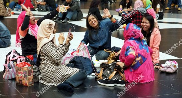 Indonesian maids gather Taipei Raiwaly Station relaxation (Shutterstock)